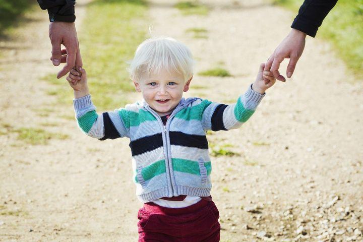 Мальчик гуляет с мамой и папой