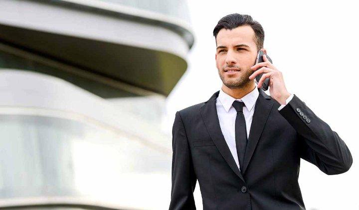 мужчина в костюме с телефоном