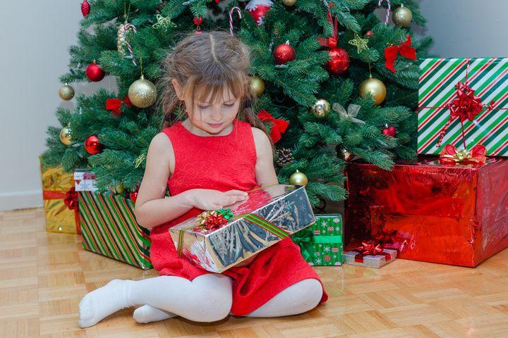 Девочка разворачивает подарки