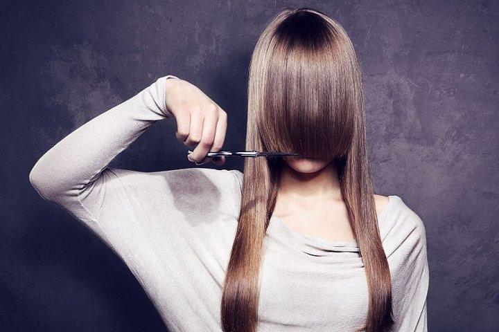 девушка стрижет челку