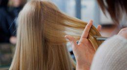 парикмахер обрезает волосы