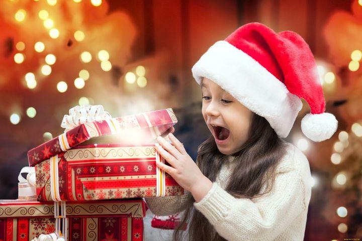 Девочка открывает новогодний подарок