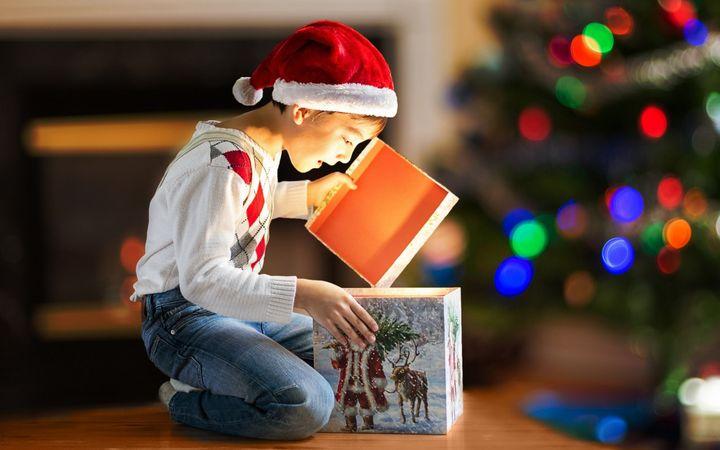 Мальчик открывает подарок на Новый год