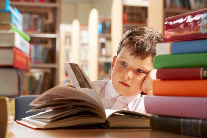 Мальчик читает книги