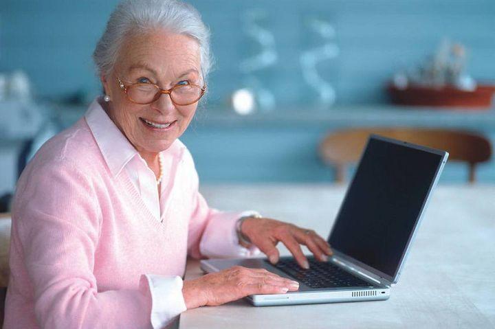 Женщина пенсионер пользуется ноутбуком