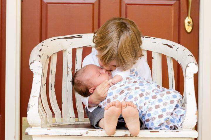 Ребенок держит новорожденного